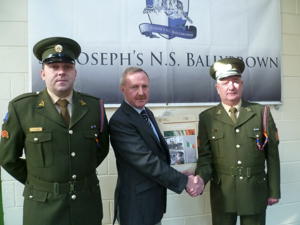 Joe Lyons accepts a special commemorative pack from Corporal O Reilly and Company Sergeant Shanahan on behalf of Ballybrown NS